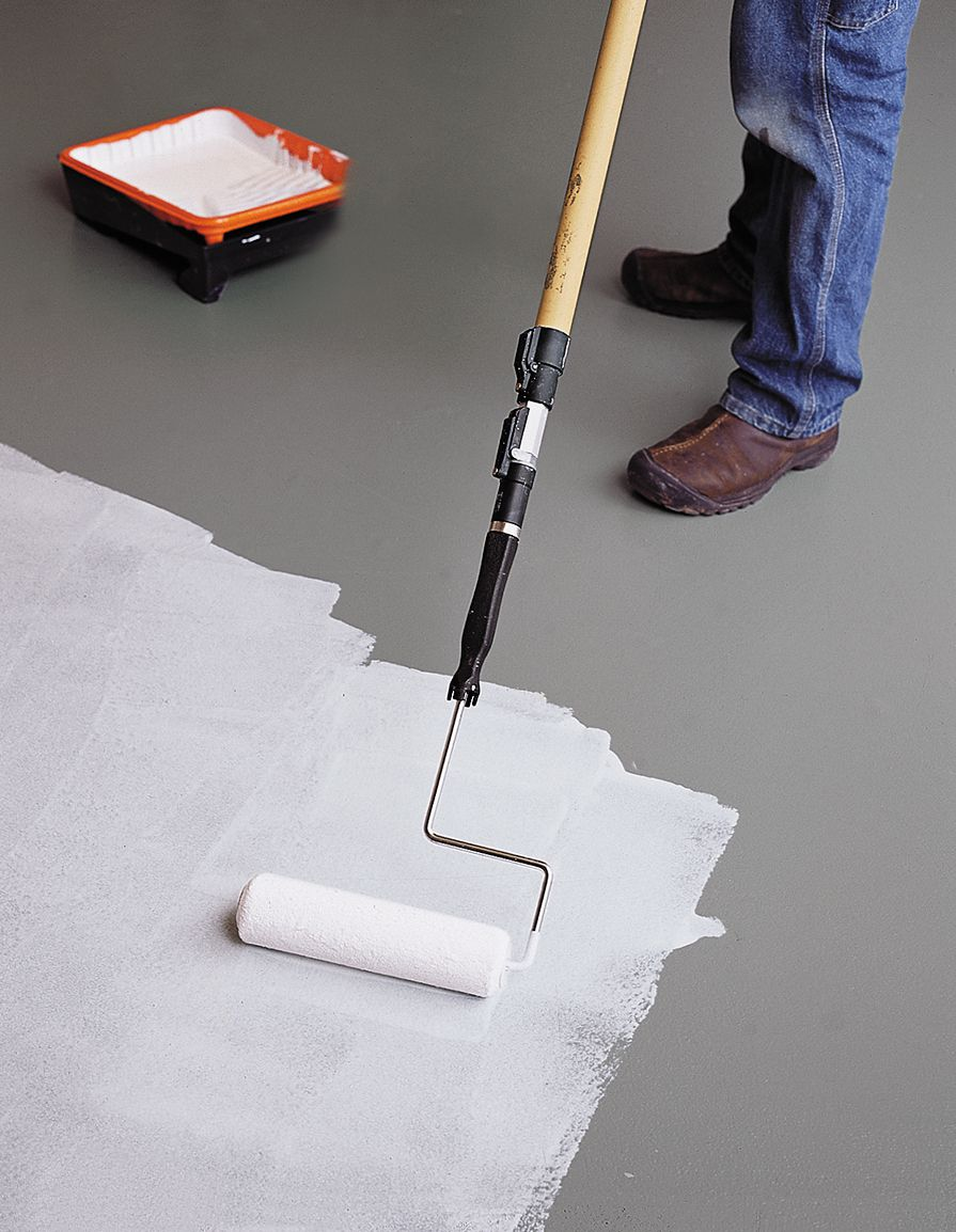 Person quickly applying top coat to garage floor with a paint roller.
