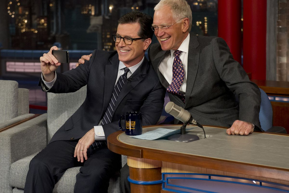 Stephen Colbert (seated) appears on The Late Show with David Letterman shortly after being named Letterman's successor.