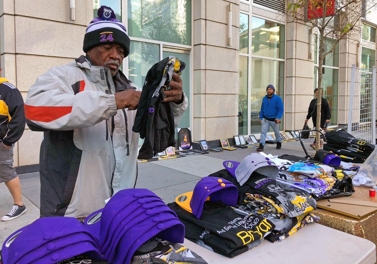 Donnell Dorsey arranges Kobe Bryant memorabilia outside the Staples Center in Los Angeles, Monday, Feb. 24, 2020. Dorsey slept along Figueroa Street Sunday night to claim a spot to sell merchandise outside the public memorial for Kobe Bryant and his daughter, Gianna. Dorsey said he sold out of Bryant-related T-shirts and hats five times the day after the basketball superstar died. (AP Photo/Stefanie Dazio)