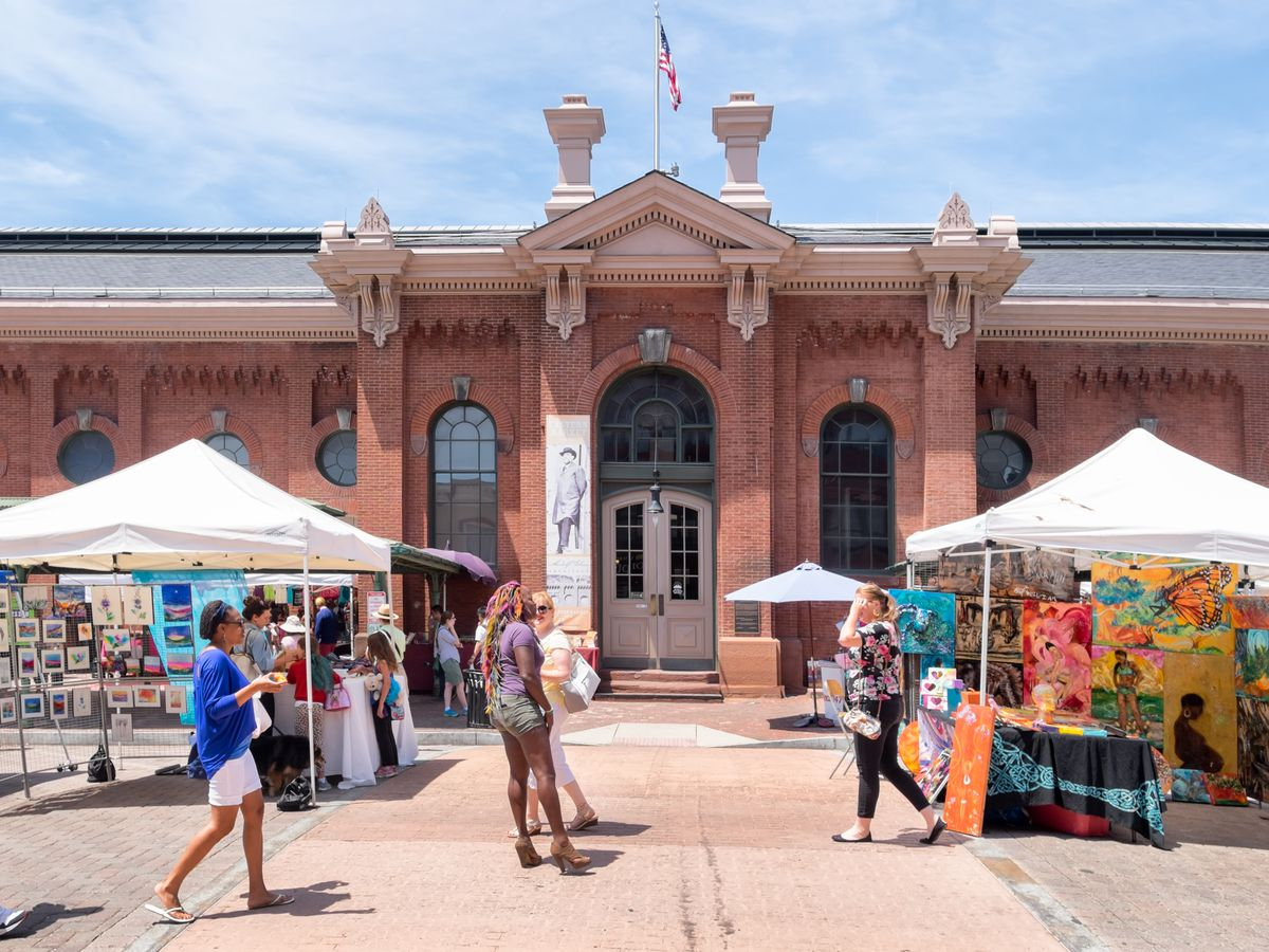 The exterior of Eastern Market in Washington D.C. The facade is red with arched windows and doors.