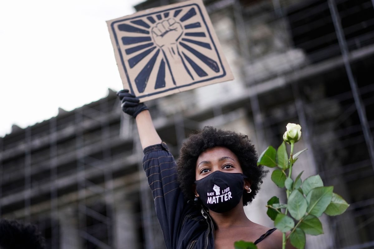 A masked protester holds up a single rose and a sign displaying art representing a fist in the middle of radiating lines.