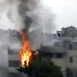 In this image made from amateur video released by the Shaam News Network and accessed Sunday, April 15, 2012, a building is on fire following purported shelling in Homs, Syria. Syrian troops are reported to have shelled residential neighborhoods dominated by rebels in the central city of Homs Sunday, activists said, killing at least three people hours before the first batch of United Nations observers were to arrive in Damascus to shore up a shaky truce.
