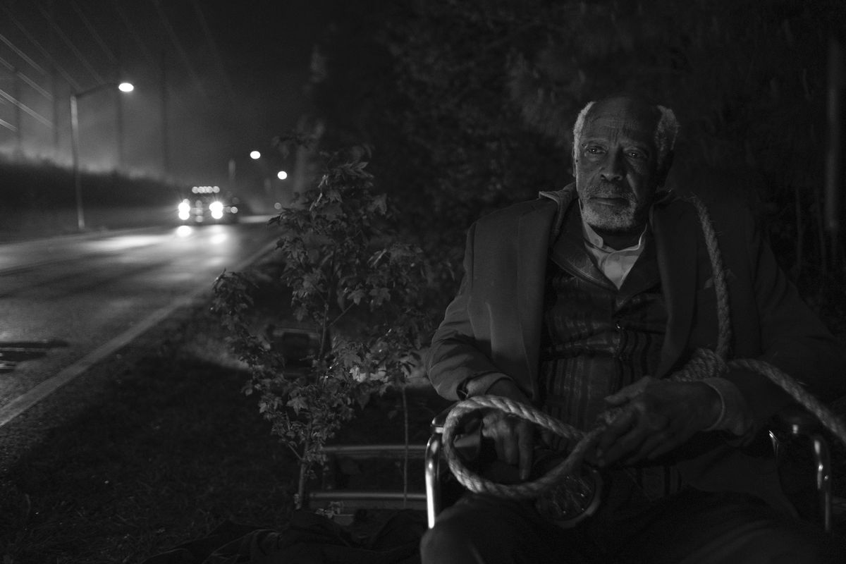 an old will sits on the side of the road in his wheelchair, holding a noose