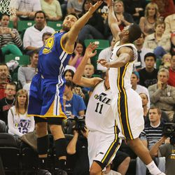 Utah's Alec Burks and Warriors' Andrew Bogut battle for a rebound as the Utah Jazz and the Golden State Warriors play Tuesday, Oct. 8, 2013 in preseason action at Energy Solutions arena in Salt Lake City.