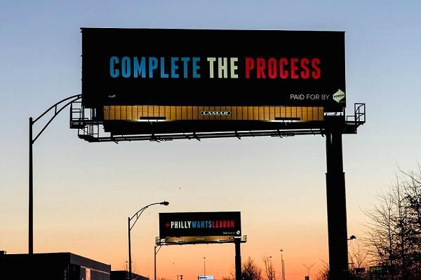 """A billboard reading, """"COMPLETE THE PROCESS"""""""