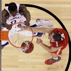 Kansas forward Thomas Robinson (0) slam dunks over Ohio State guard Aaron Craft (4) during the second half of an NCAA Final Four semifinal college basketball tournament game Saturday, March 31, 2012, in New Orleans.