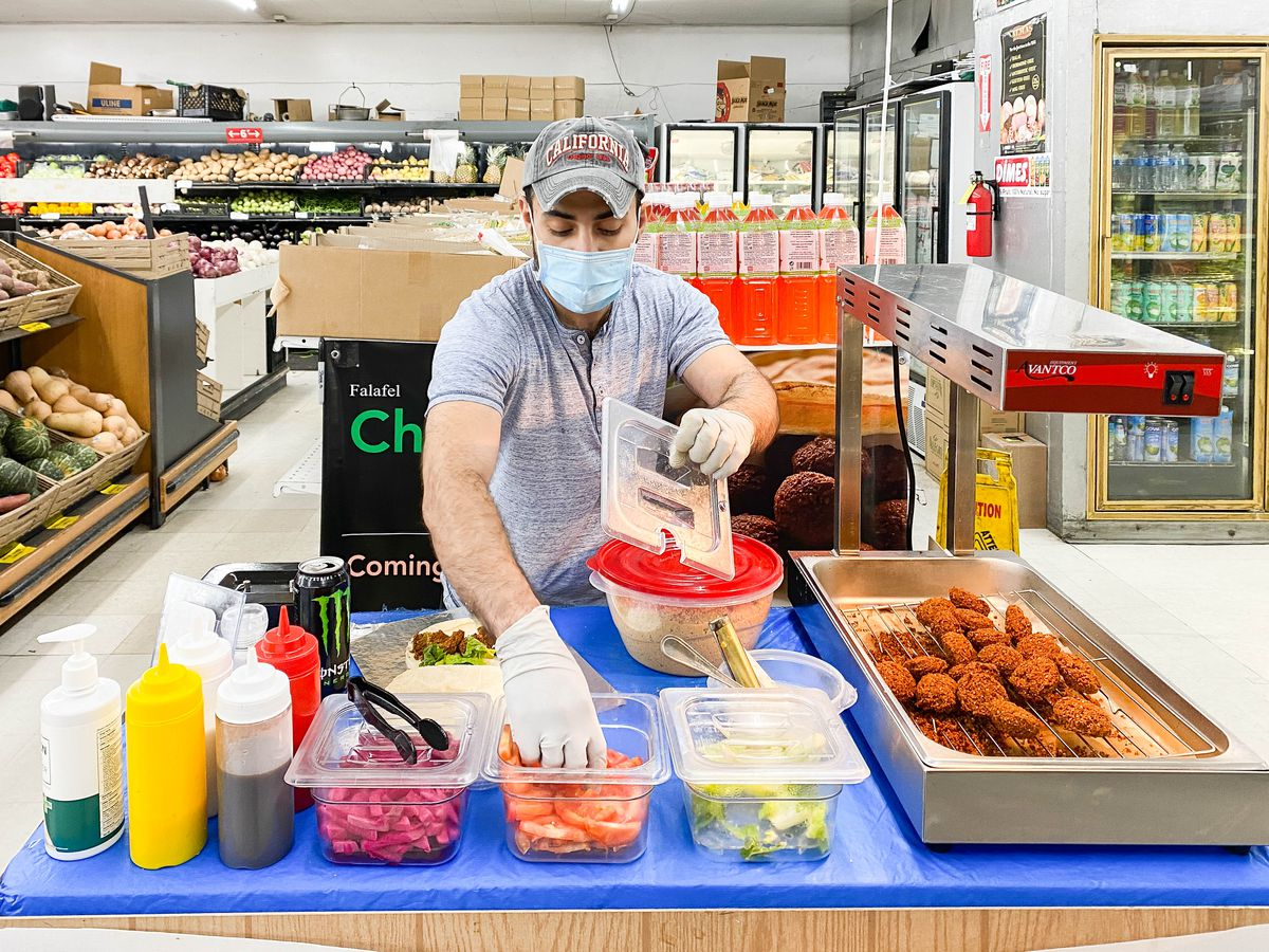 A man in hat and mask makes a falafel sandwich inside of a market.