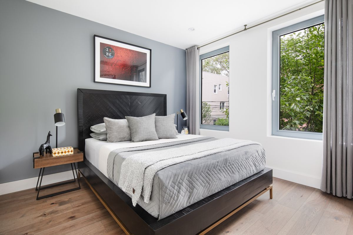 A bedroom with a large bed, two windows, hardwood floors, and white and grey walls.