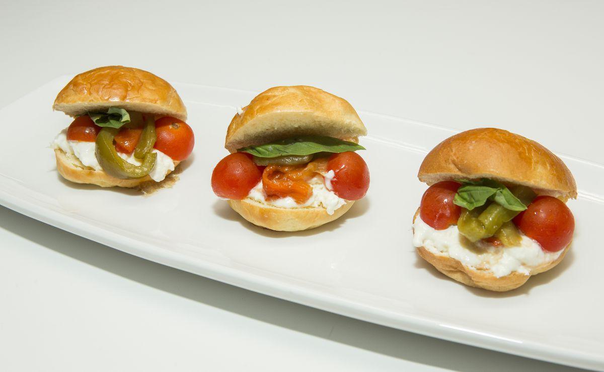 Three Italian mozzarella cheese, tomato, and basil sandwiches brown buns sit on a long white plate.
