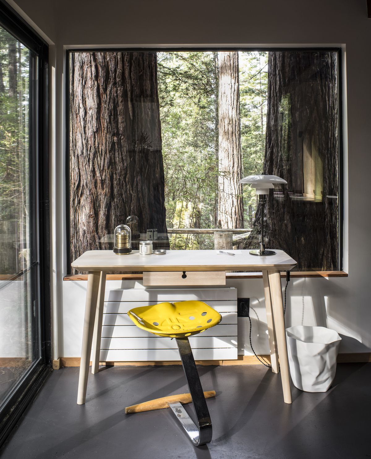 A light-colored wood desk sits in a corner. It has a modern desk lamp and a yellow-and-chrome stool with a metal tractor seat.