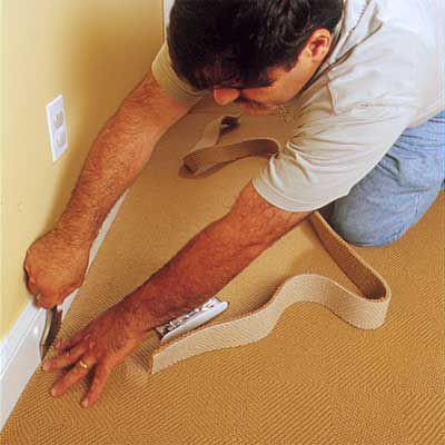 Man Uses Carpet Chisel To Force Edge Of Carpeting Into Space Beneath Baseboard Molding