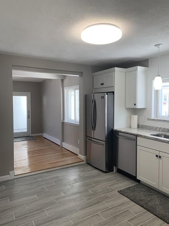A recently renovated kitchen leading into an empty living room.