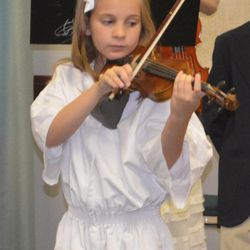 Abigail McLaughlin, now 8, playing the violin at her LDS baptism, in October 2012.