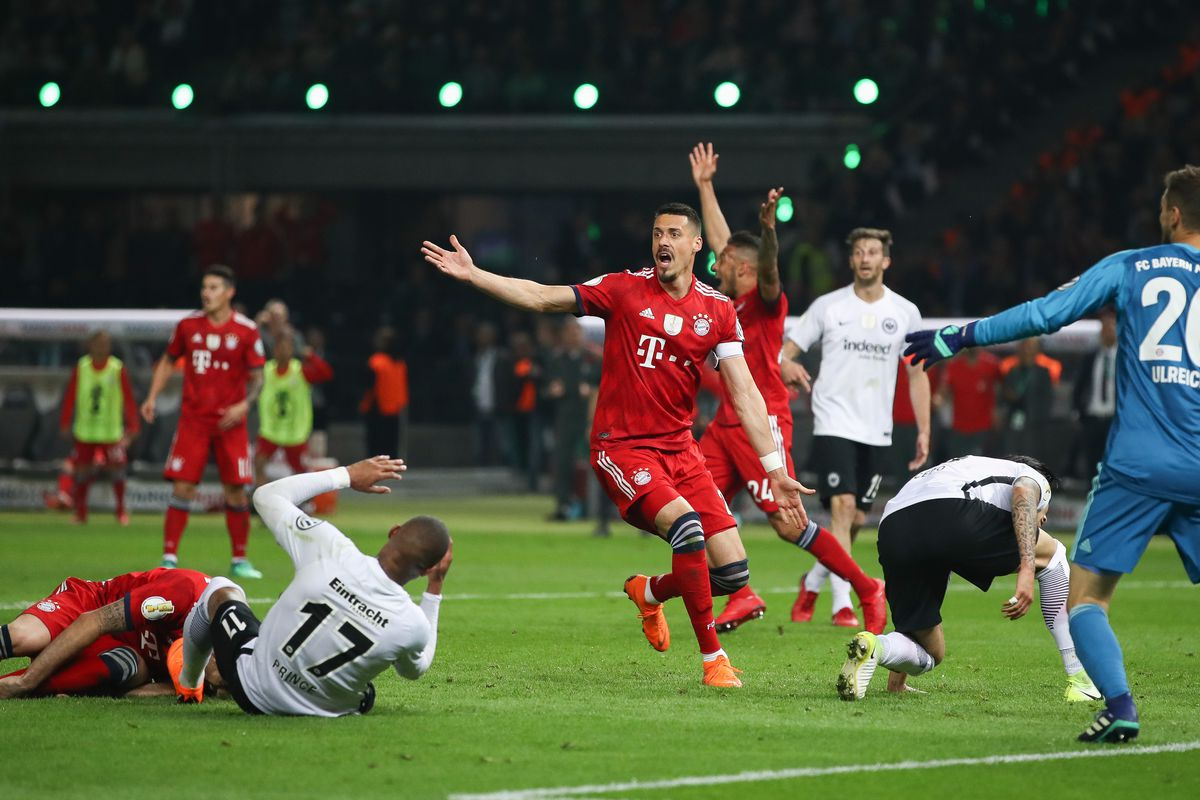 BERLIN, GERMANY - MAY 19: Sandro Wagner #2 of FC Bayern Muenchen reacts as Javi Martinez #8 of FC Bayern Muenchen and by Kevin-Prince Boateng #17 of Eintracht Frankfurt lay on the pitch during the DFB Cup final between Bayern Muenchen and Eintracht Frankfurt at Olympiastadion on May 19, 2018 in Berlin, Germany.