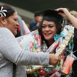 Gloria Tonuga gives her daughter, Katrina, gifts after Salt Lake Community College's commencement ceremony at the Maverik Center in West Valley City on Friday, May 6, 2016.