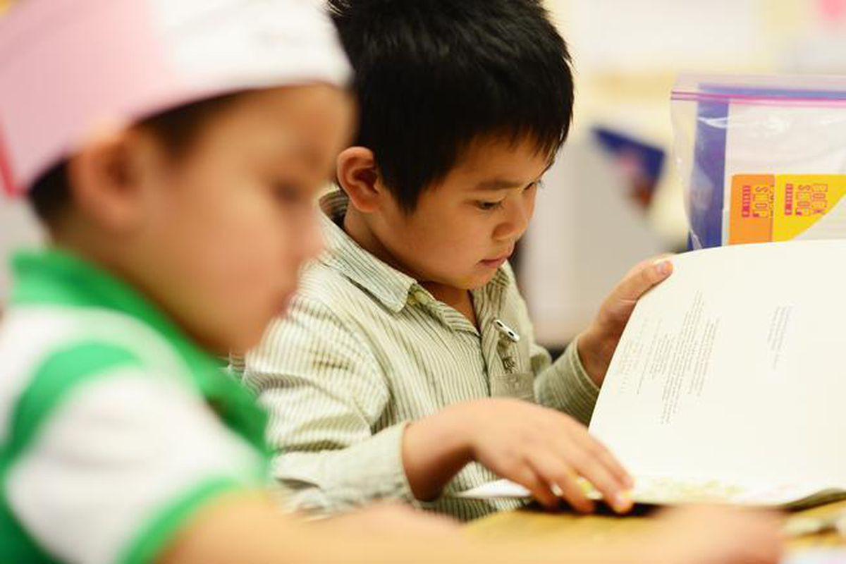 A kindergartner flips the page while reading in class at Crawford Elementary in Aurora.