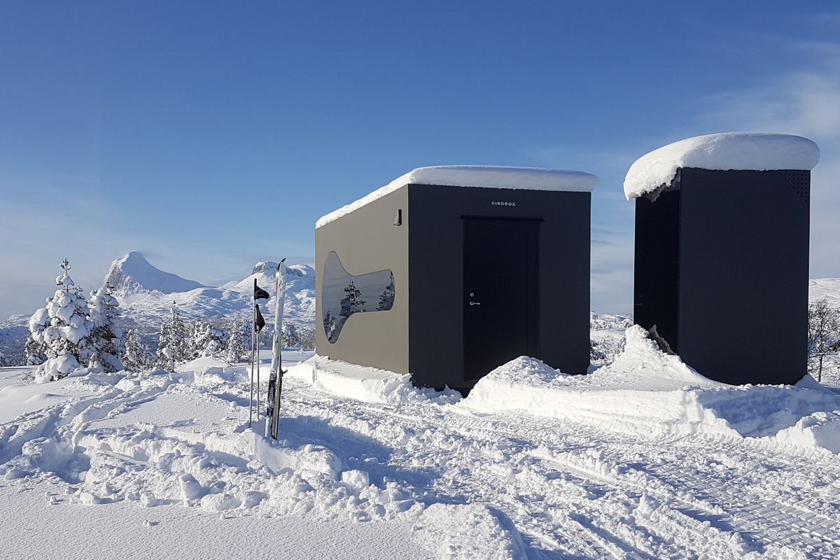 Two black boxes in a snowy landscape.