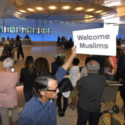 John Wider holds up a sign becoming Muslims in the Tom Bradley International Terminal at Los Angeles International Airport, Thursday, June 29, 2017, in Los Angeles. A scaled-back version of President Donald Trump's travel ban took effect Thursday evening, stripped of provisions that brought protests and chaos at airports worldwide in January yet still likely to generate a new round of court fights.