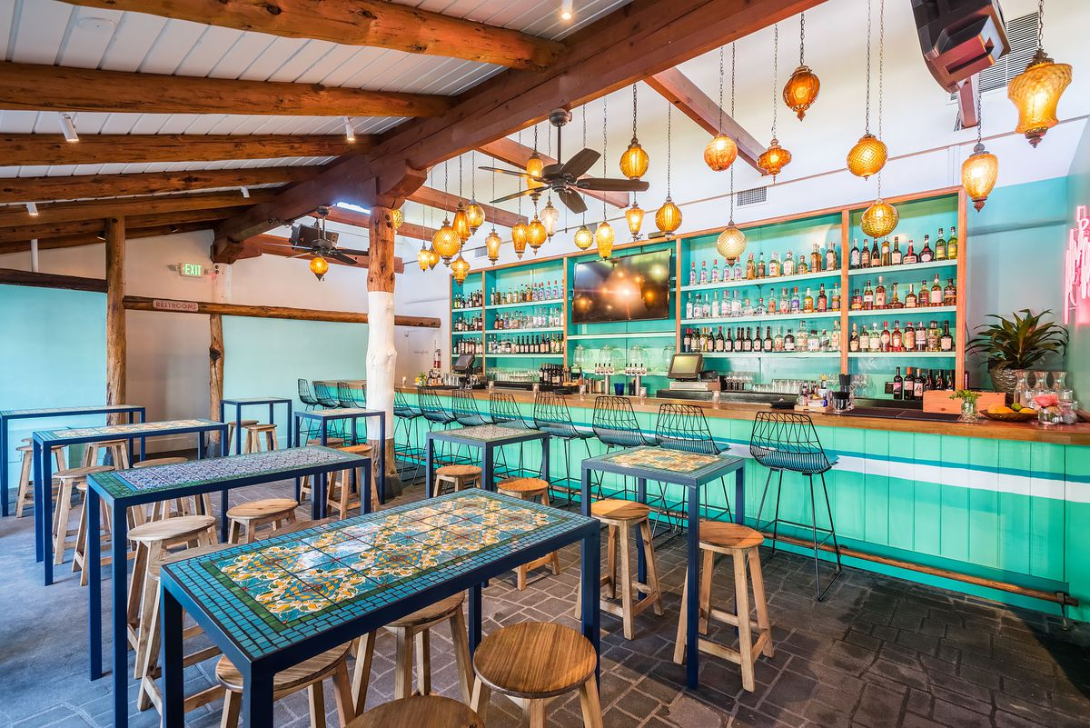 Tallula's bar and high top tables with teal color and hanging orange votives.