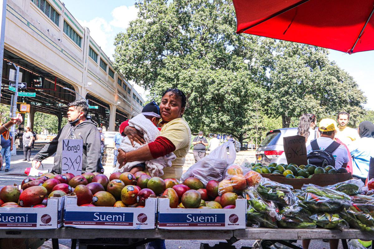 A woman holding a baby stands behind several trays with produce, including mangos and plantains
