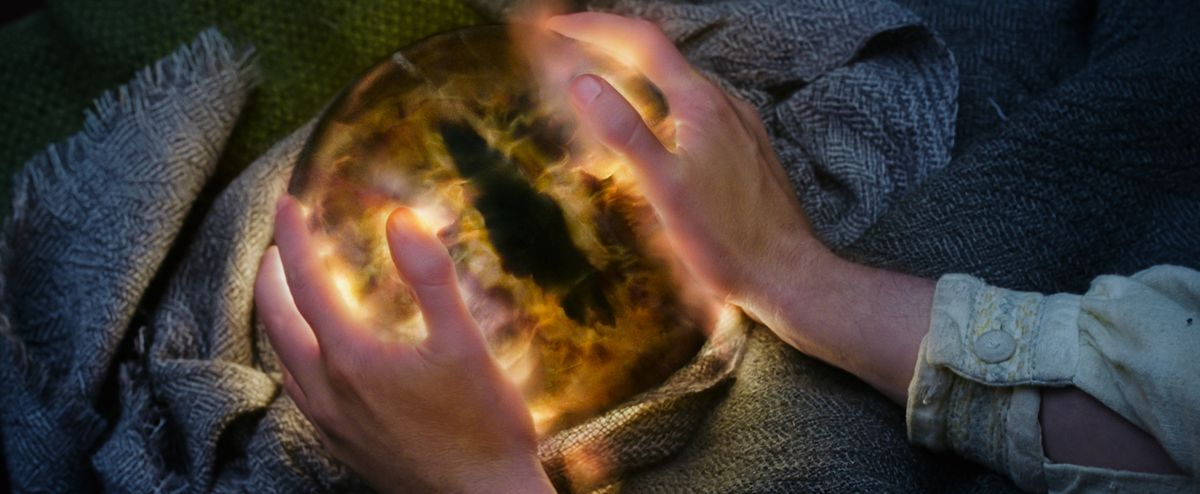Sauron's eye ball with Pippin's hands on it in Lord of the Rings