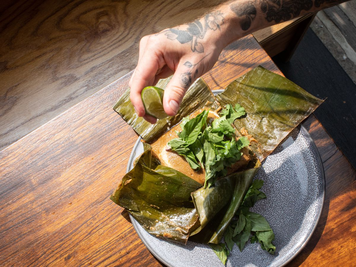 A dish of fish smothered in orange curry set on an unwrapped banana leaf on top of a blue plate on a wooden table. A tattooed hand squeezes lime over the fish