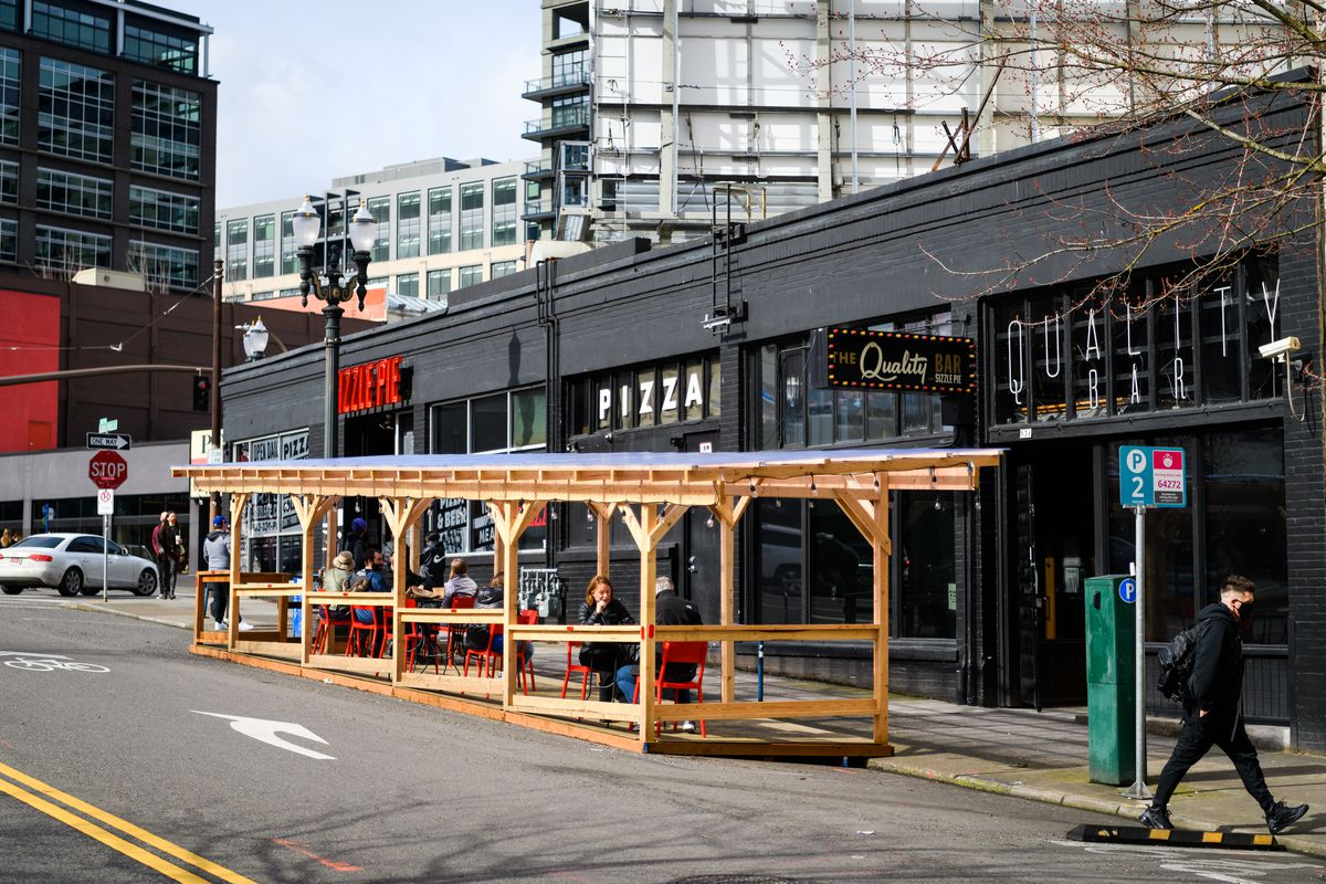 A wooden structure with a roof sits outside Sizzle Pie in Portland, Oregon