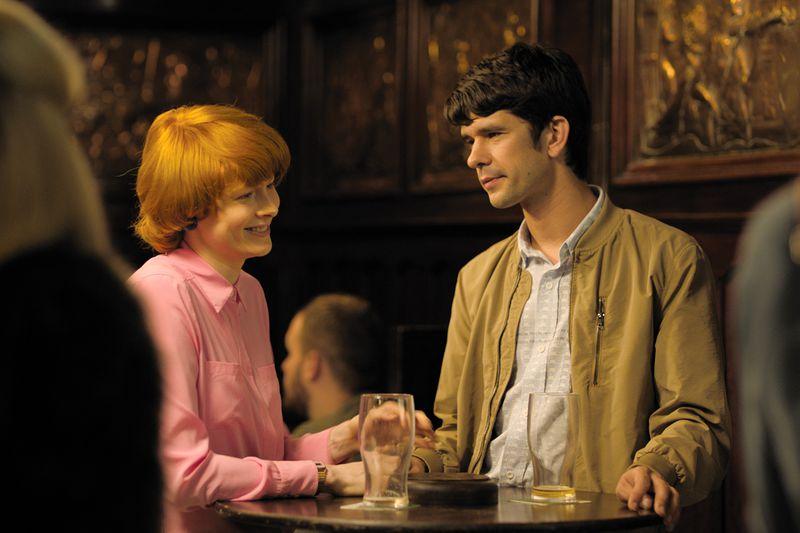 A woman and a man at a bar, laughing.