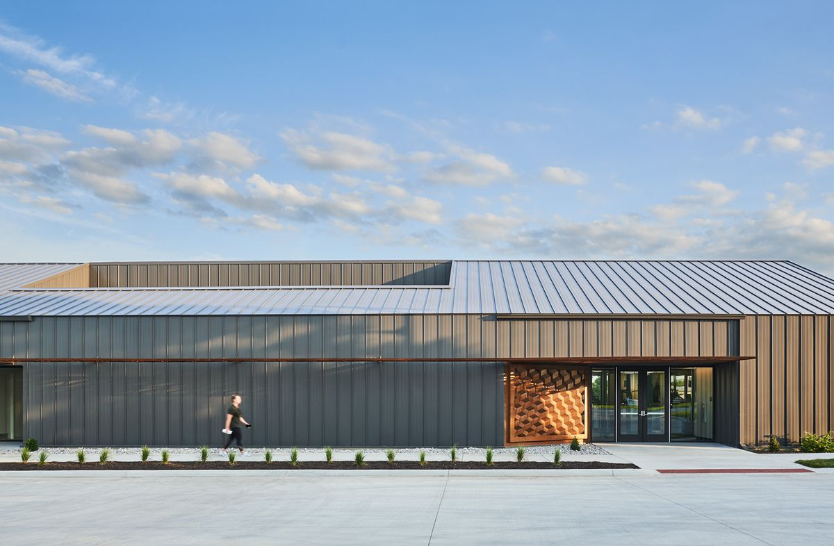 A person walks in front of a long, low-slung building clad in standing-seam gray metal.