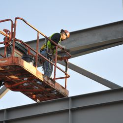 Steel worker in left field, securing a support beam -