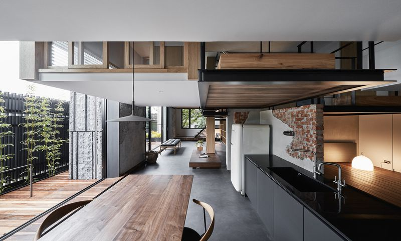 An open kitchen with black counters and a wooden table. Living spaces dangle from above.