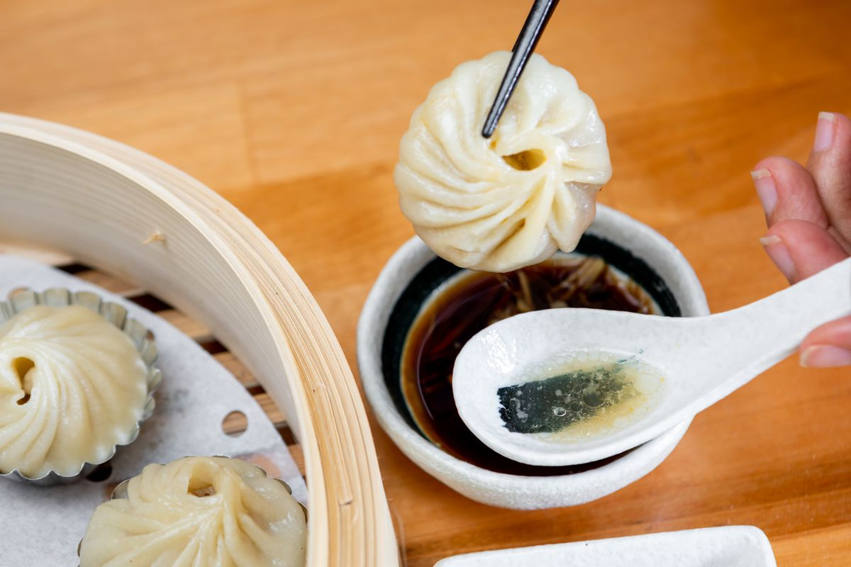 A view of the delicate pleating of a xiao long bao, held over a soup spoon by a pair of chopsticks