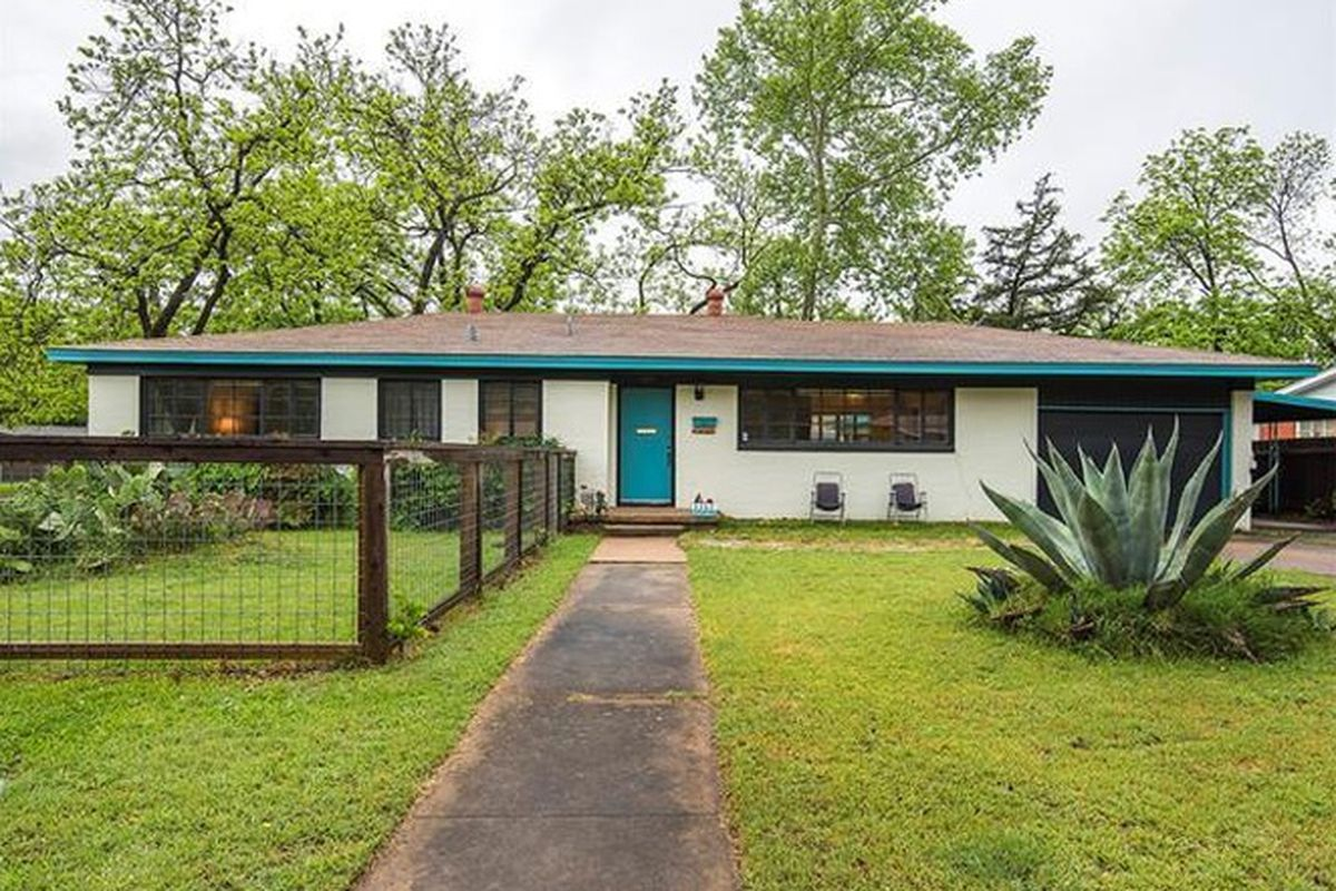 low-slung, white brick 1950s ranch style house with aqua trim, garage/carport, fenced on one side