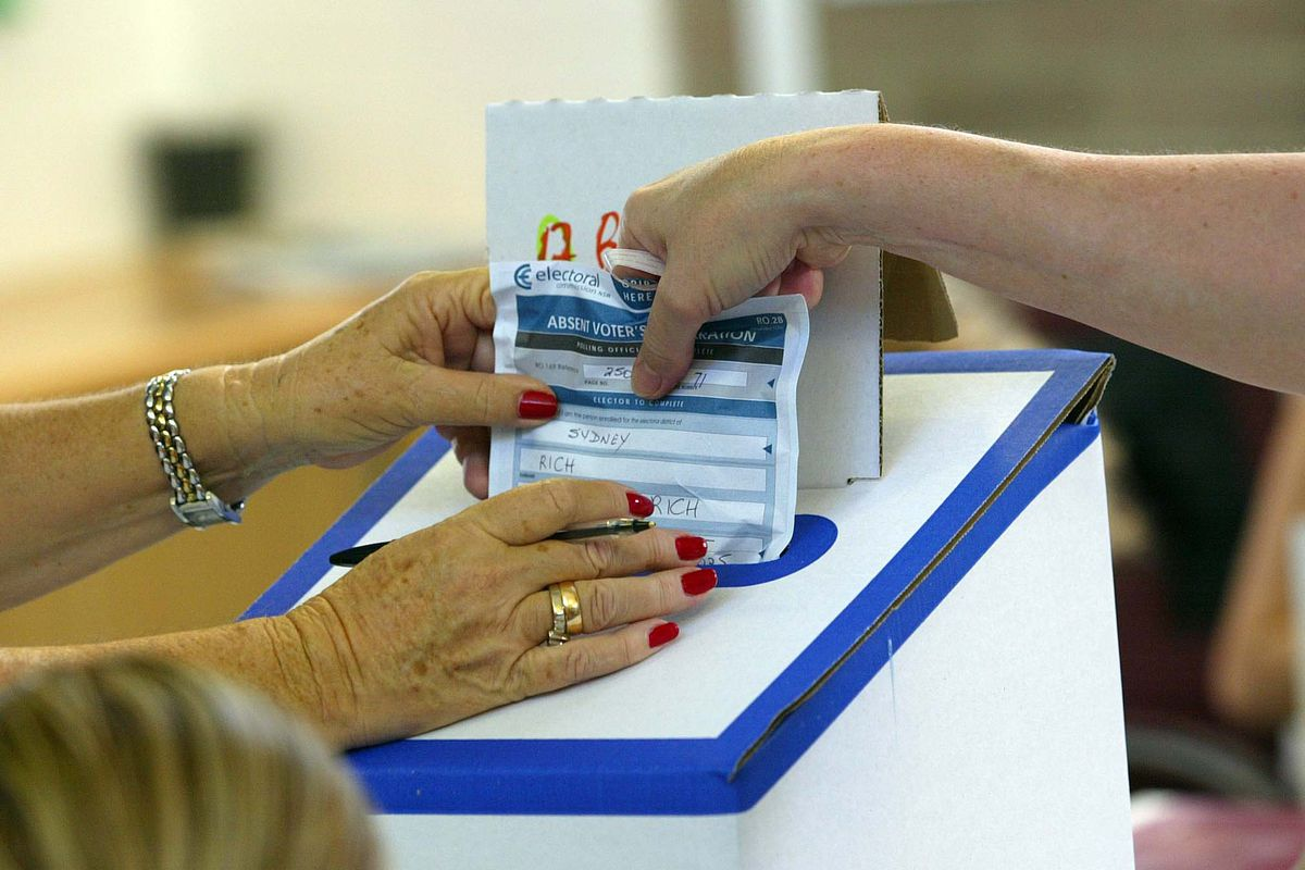 NSW State Election 2007. A voter places their absentee vote in the ballot box at