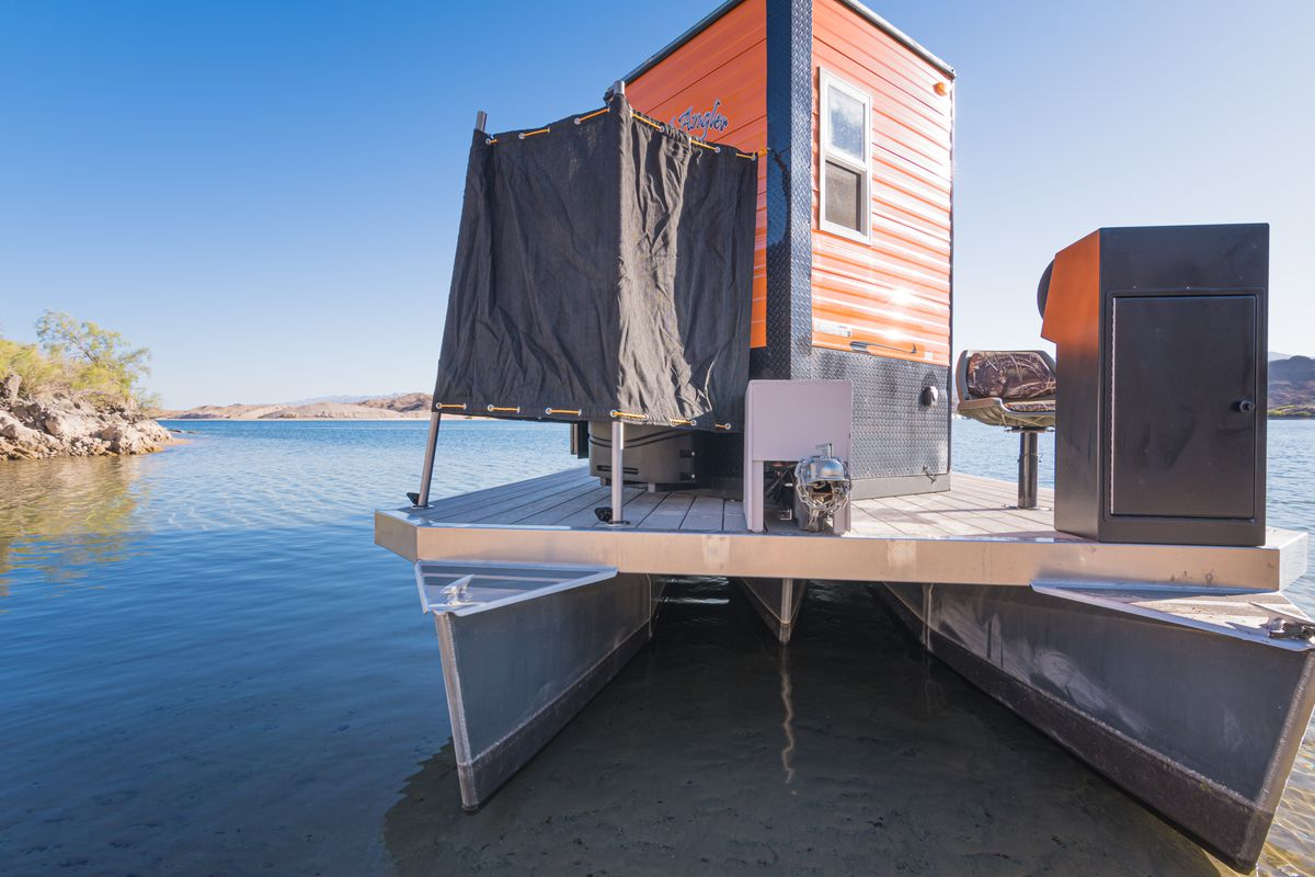 The rear view of the boat features an outside shower area and water views.