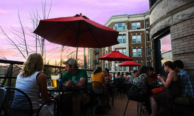 a small restaurant roof deck with red umbrellas is pictured at sunset, with a high-rise apartment building visible behind it