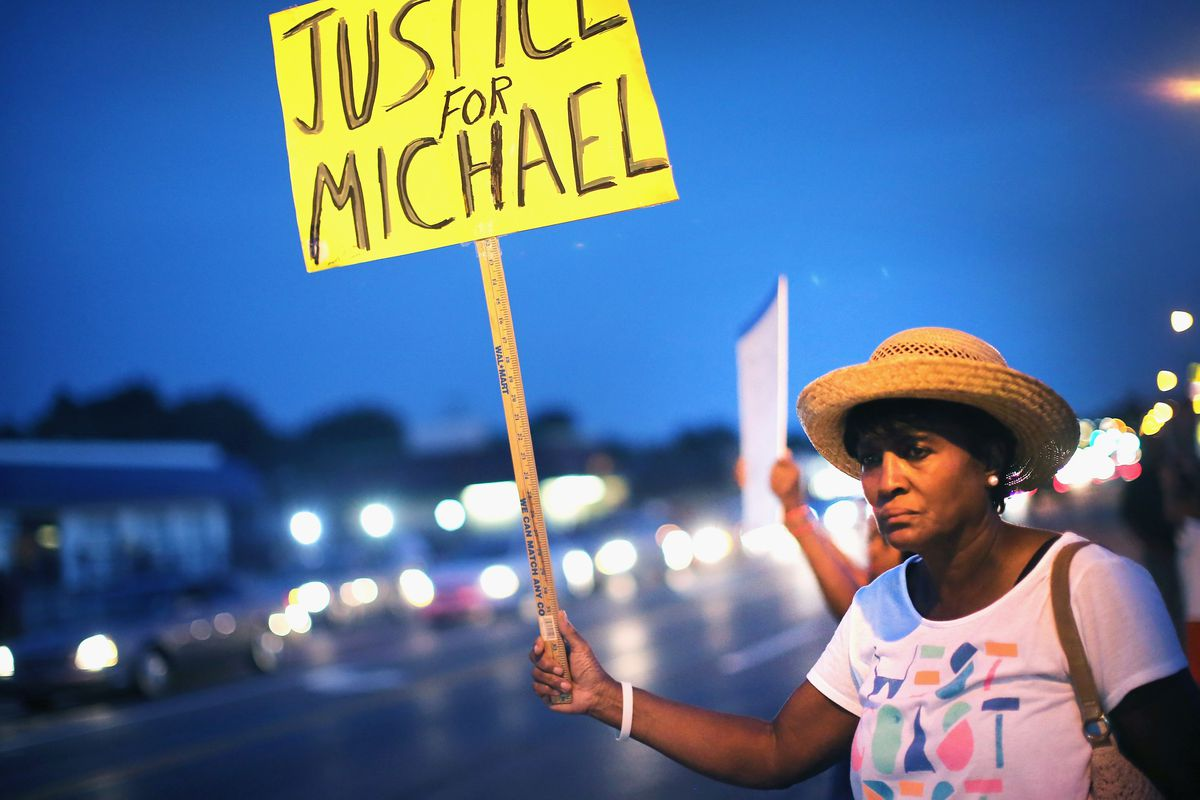 FERGUSON, MO - AUGUST 14: Gwen Stewart joins other demonstrators along West Florissant Avenue to protest the shooting death of Michael Brown on August 14, 2014 in Ferguson, Missouri.