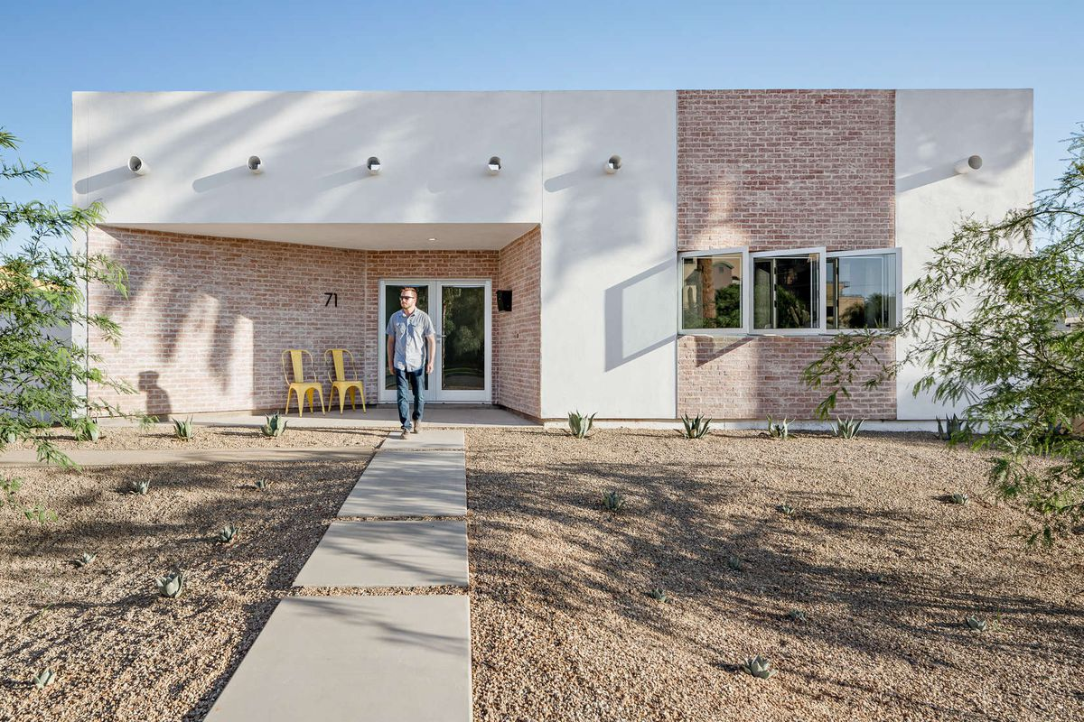 Exterior shot of front of boxy one-story home featuring a recessed entrance with flared walls lined with brick and three small windows puncturing the wall on the other side.