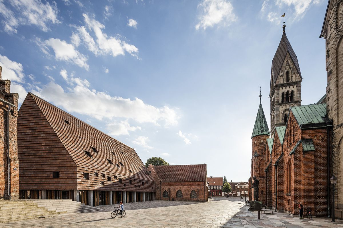 A building with an oversized brick gabled roof structure in front of an old cathedral.
