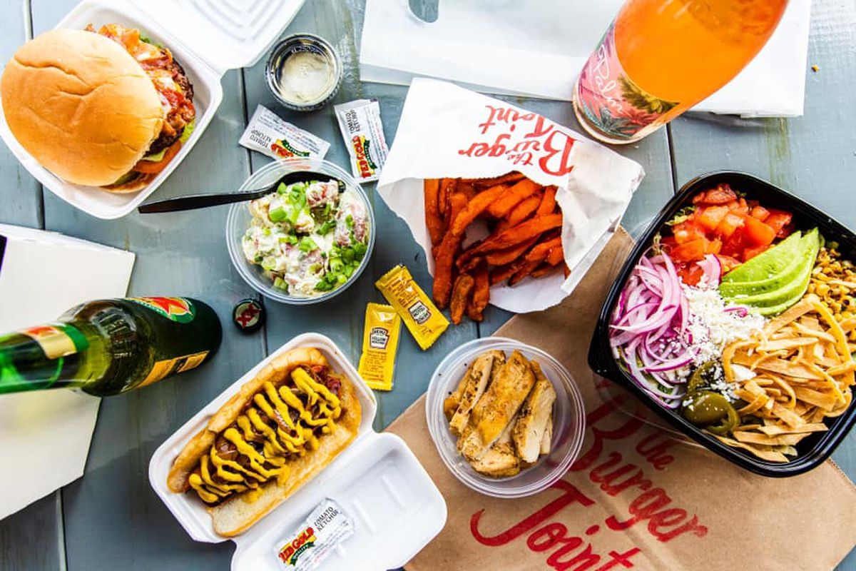 a birdseye view of a table full of food from a local burger restaurant include a hamburger, mustard packets, a Dox XX, a mustard-drizzled hot dog, sweet potato fries and salad topped with red onions, sliced avocado, tomatoes, corn, jalapeños and tortilla strips