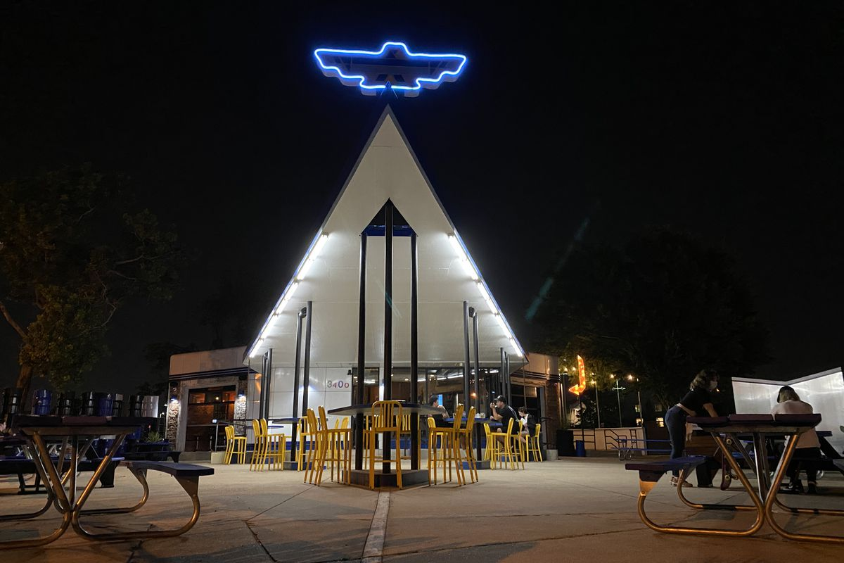 A white a-frame roof set against a dark sky backdrop. Atop the A-frame is a blue neon thunderbird shape.