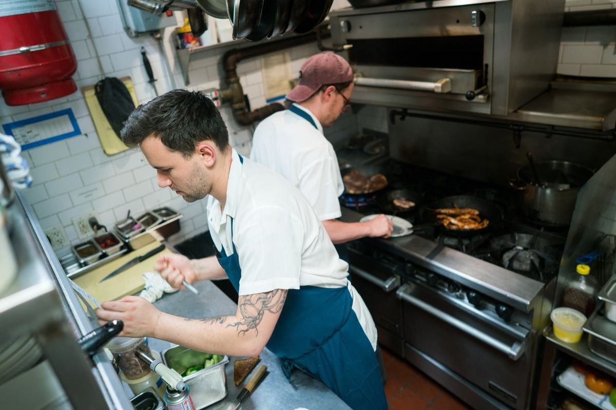 One chef cooking at a stove with another in the foreground