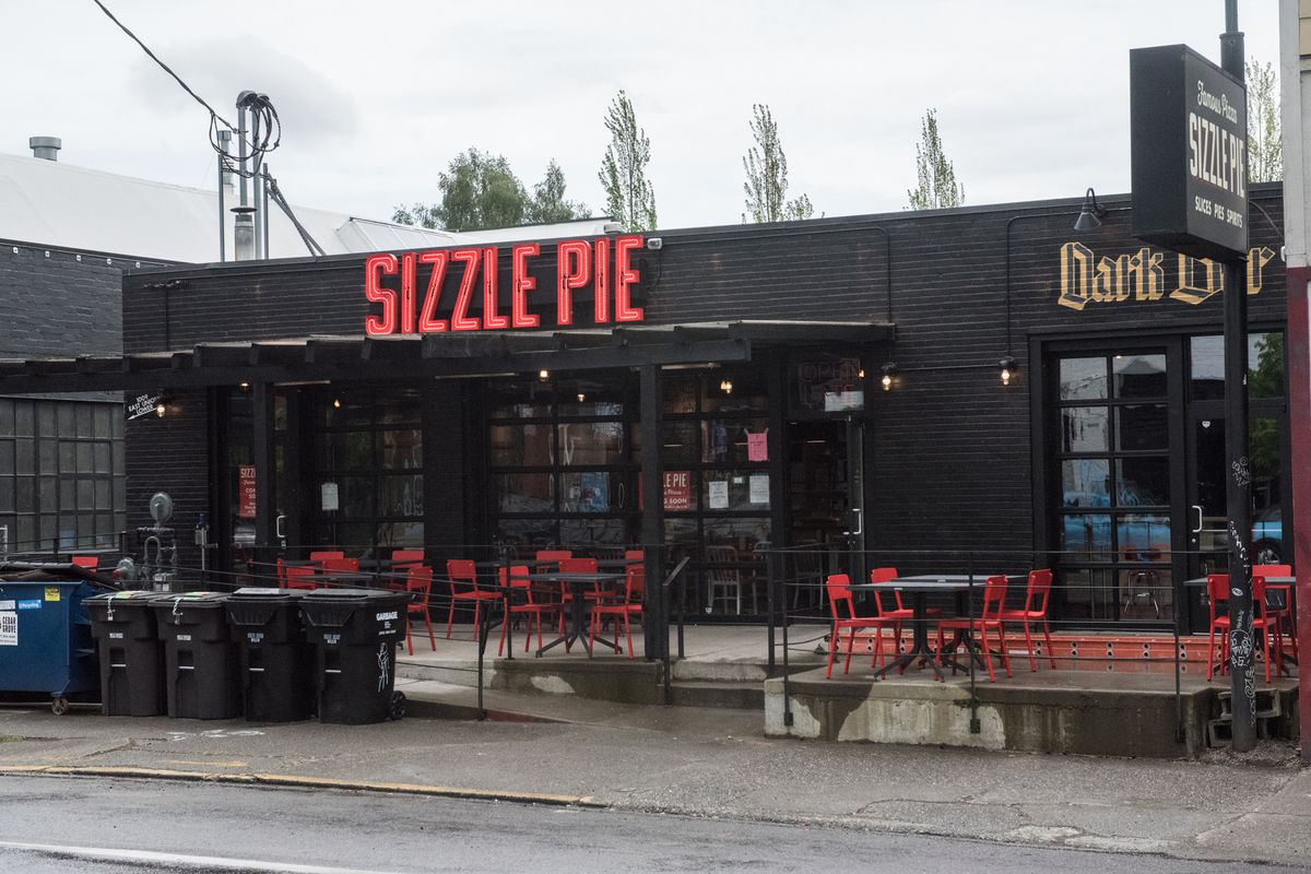 An exterior look at Sizzle Pie on Capitol Hill on a cloudy day, with the restaurant's red neon sign displayed prominently.
