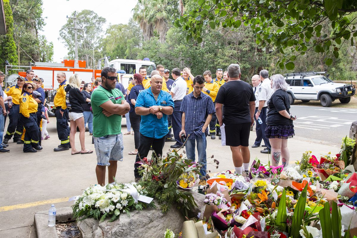 Civilians and firefighters in Sydney, Australia, gather around a collection of flower bouquets in memory of two volunteer firefighters who died fighting bushfires.