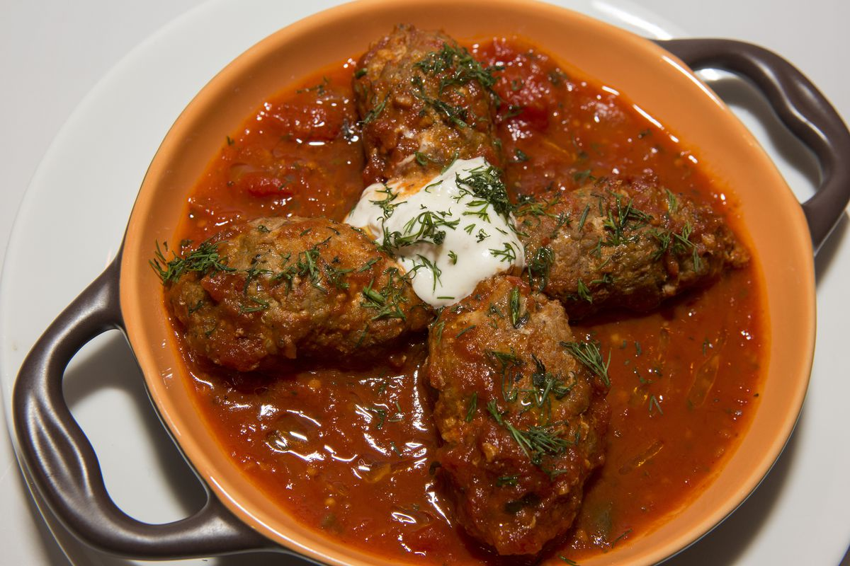 Four oblong-shaped Greek meatballs in tomato sauce with a dollop of cheese.