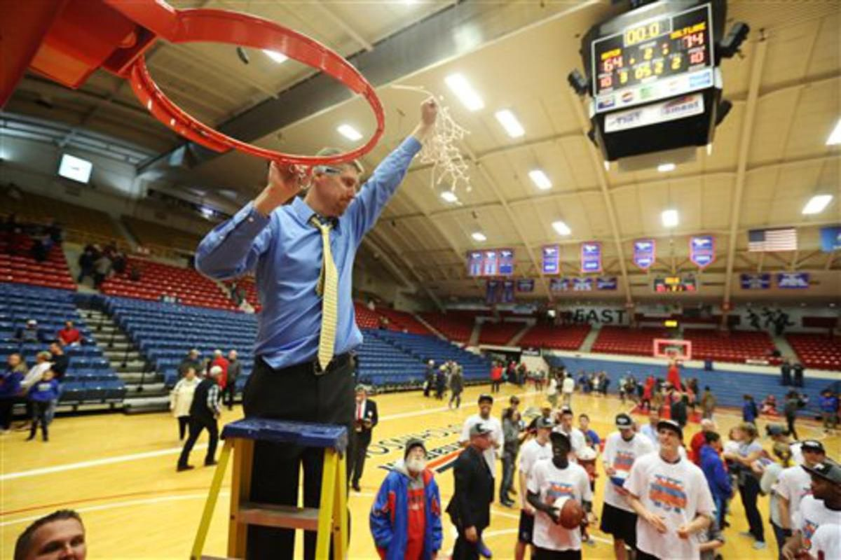 Salt Lake coach Todd Phillips lifts the net after cutting it down after the team defeated Hutchinson in the NJCAA basketball tournament final, 74-63, Saturday, March 19, 2016, in Hutchinson, Kan. (Travis Morisse/The Hutchinson News via AP)