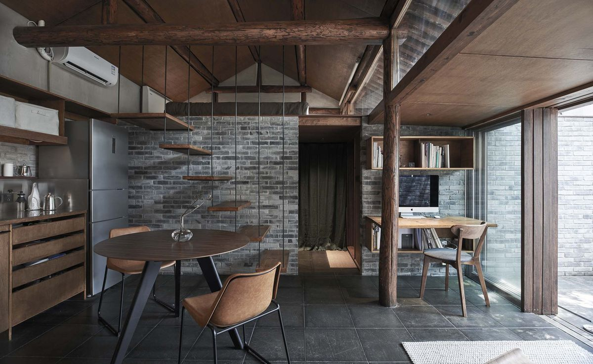 Living room with dark tile floors and wooden furniture.
