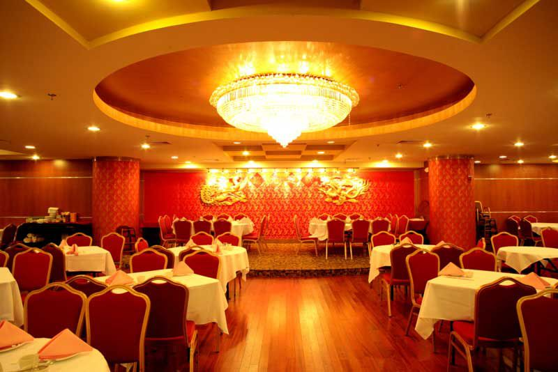 A large room with wood flooring and white tablecloth-adorned tables has red walls and a central chandelier