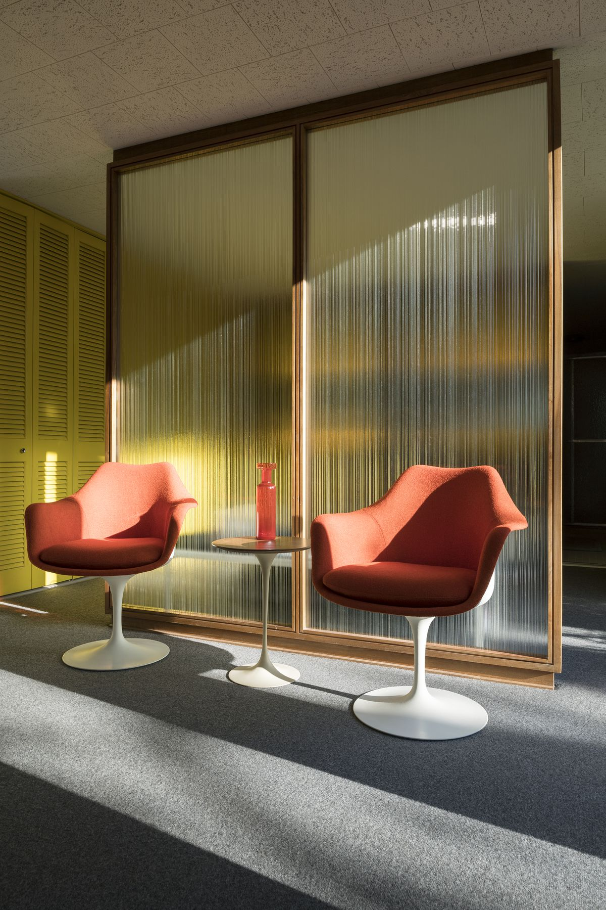 Two chairs sit in front of a rippled glass screen.