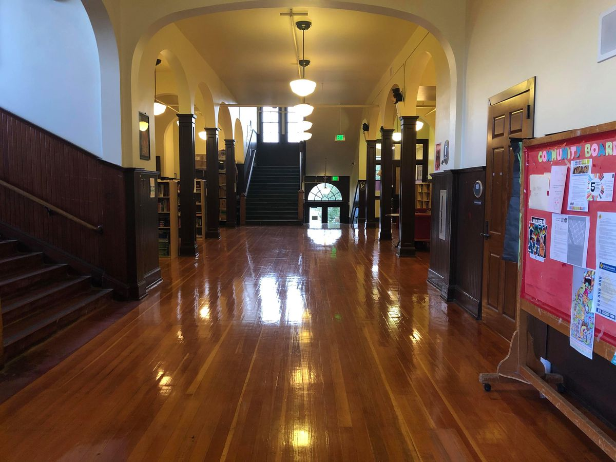 A tall, wide hallway with hardwood floors. There's an arch partway down, and an open stairwell leading up to a landing and down a half-floor at the far end. Archways line the left and right in between. A staircase leads up to the left in the foreground.